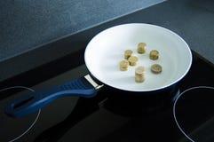 Cuisson des euros dans une casserole Image libre de droits