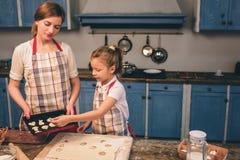 Cuisson des gâteaux faits maison La famille affectueuse heureuse préparent la boulangerie ensemble La fille de fille de mère et d Photos stock