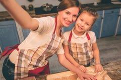 Cuisson des gâteaux faits maison La famille affectueuse heureuse préparent la boulangerie ensemble La fille de fille de mère et d Photo libre de droits