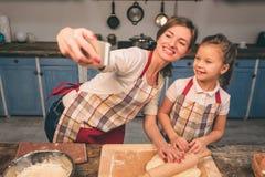Cuisson des gâteaux faits maison La famille affectueuse heureuse préparent la boulangerie ensemble La fille de fille de mère et d Images libres de droits