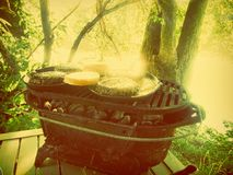 Cuisson des hamburgers d'hamburgers sur le barbecue de gril dans la nourriture de camping de camp de forêt en bois Images stock