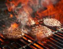 cuisson des hamburgers sur le gril chaud avec des flammes photo libre de droits