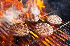 cuisson des hamburgers sur le gril chaud avec des flammes photo stock