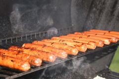 Cuisson des hot dogs sur le gril ! Photo libre de droits