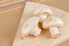 Cuisson des ingrédients, trois champignons de couche blancs Photographie stock libre de droits