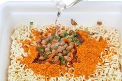 Cuisson des nouilles instantanées dans la tasse de mousse Image libre de droits
