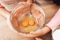 Cuisson des petits gâteaux dans la cuisine Les mains du ` s de femelle et d'enfants tiennent la cuvette avec des oeufs Photos libres de droits
