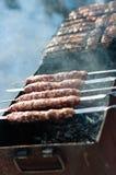 Cuisson des saucisses sur des brochettes Images libres de droits