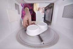 Cuisson du braconnier d'oeufs dans votre micro-onde photographie stock