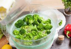 Cuisson du brocoli dans le vapeur dans la cuisine Photos stock