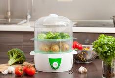 Cuisson du brocoli et des pommes de terre dans le vapeur dans la cuisine Photo stock