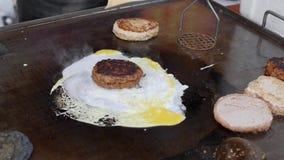 Cuisson du cheeseburger spécial avec l'oeuf Boeuf ou porc grand, côtelette luxuriante et délicieuse grillant sur la casserole clo banque de vidéos