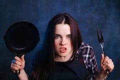 Cuisson du concept Jeune femme au foyer fâchée ou choquée avec la casserole et le g image stock