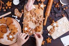 Cuisson du pain d'épice de Noël Amis décorant fraîchement cuit au four Photo stock