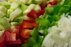 Cuisson du poivre, de l'oignon, du concombre et de la courgette faisant la nourriture saine avec les légumes coupés Dîner estival photos stock