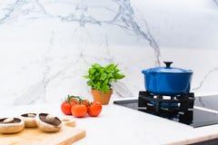 Cuisson du pot et des ingrédients sur le banc de marbre de cuisine photo stock