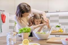 Cuisson du repas ? la maison sain par la famille Enseignement de femme et aider la fille à saler et poivrer une salade fraîche photographie stock libre de droits