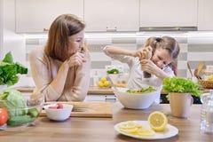 Cuisson du repas ? la maison sain par la famille Les sels de fille ont fraîchement fait cuire la salade, la mère recherche et se  image stock
