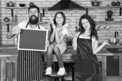 Cuisson ensemble Les tabliers d'usage de papa et de fille de maman de famille se tiennent dans la cuisine Cuisson du concept de n photographie stock