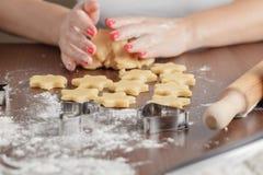 Cuisson et concept à la maison - fermez-vous des mains femelles faisant le cooki Image stock