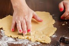 Cuisson et concept à la maison - fermez-vous des mains femelles faisant le cooki Images libres de droits
