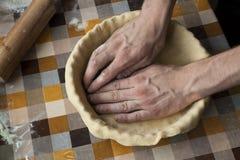 Cuisson et concept à la maison - fermez-vous des mains masculines malaxant la pâte Photographie stock