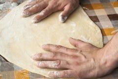Cuisson et concept à la maison - fermez-vous des mains masculines malaxant la pâte Image stock