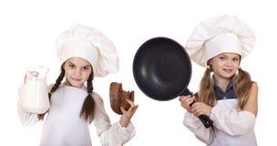 Cuisson et concept de personnes - deux petites filles dans un tablier blanc h photographie stock