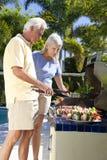 Cuisson extérieure de couples aînés heureux sur un barbecue Photo stock