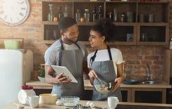 Cuisson heureuse de couples d'afro-américain et comprimé d'utilisation Photographie stock