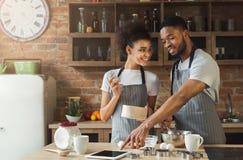 Cuisson heureuse de couples d'afro-américain et comprimé d'utilisation Images libres de droits