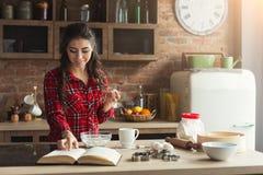 Cuisson heureuse de jeune femme dans la cuisine de grenier image libre de droits