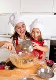 Cuisson heureuse de mère avec la petite fille dans le chapeau de tablier et de cuisinier préparant la pâte à la cuisine Photos stock