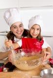 Cuisson heureuse de mère avec la petite fille dans le chapeau de tablier et de cuisinier préparant la pâte à la cuisine Photographie stock libre de droits