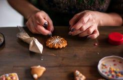 Cuisson, les gens, Noël et concept de décoration - fermez-vous de la femme heureuse faisant des maisons de pain d'épice à la mais Photos libres de droits
