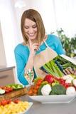 Cuisson - livre de cuisine de sourire de fixation de femme Photographie stock libre de droits