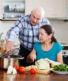 Cuisson mûre de couples   dans la cuisine Images stock