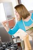 Cuisson - sauce à échantillon de jeune femme dans la cuisine Photo stock