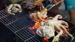 Cuisson sur griller le poulpe au marché asiatique de rue extérieure la nuit Fruits de mer de barbecue 4K clips vidéos