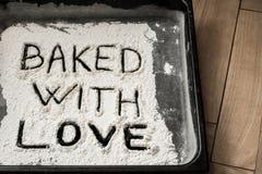 Cuit au four avec amour Word écrit sur la plaque de cuisson couverte de la farine blanche Photos libres de droits