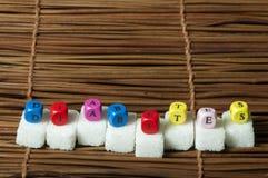 Cukier gomółki i słowo cukrzyce Fotografia Stock