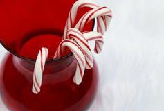 Cukierek trzciny w czerwonej szklanej wazie na białym tle Zdjęcie Stock