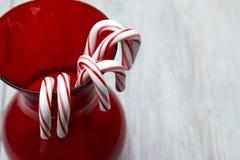 Cukierek trzciny w czerwonej szklanej wazie z białym tłem Obraz Royalty Free