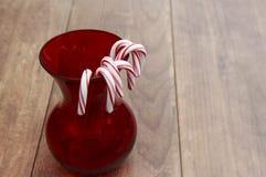 Cukierek trzciny wiesza na czerwonej szklanej wazie z drewnianym tłem Obrazy Stock