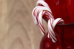 Cukierek trzciny wiesza na czerwonej szklanej wazie z drewnianym tłem Obraz Royalty Free