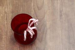 Cukierek trzciny wiesza na czerwonej szklanej wazie z drewnianym tłem Zdjęcie Royalty Free