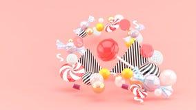 Cukierek wśród kolorowych piłek na różowym tle obrazy stock