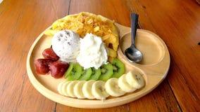 Cukierki woda nalewa na gofrze z lody i owoc wliczając bananów, kiwi i truskawek w drewnianym talerzu na stole, zdjęcie wideo