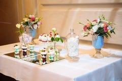Cukierku bar, stół z cukierkami i desery na stole, Bufet z wyśmienicie babeczkami, tort strzela, ciastka, kwiaty obraz royalty free