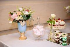 Cukierku bar, stół z cukierkami i desery na stole, Bufet z wyśmienicie babeczkami, tort strzela, ciastka, kwiaty zdjęcia royalty free